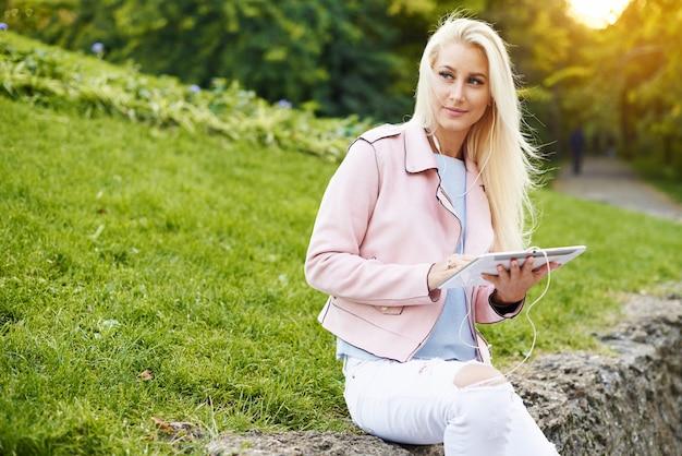 Усмехаясь музыка красивой женщины слушая расслабляющая в наушниках с ее мобильным телефоном или таблеткой на парке. студент слушает онлайн лекцию и готовится к экзаменам.