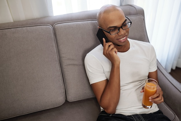 Smiling handsome young black man sitting on sofa, drinking fresh carrot juice and talking on phone with friend