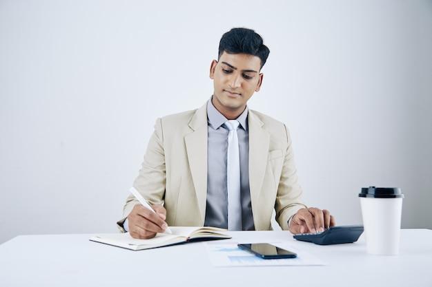 웃고 있는 잘생긴 젊은 사업가가 사무실 책상에 앉아 계산을 하고 플래너에 글을 씁니다.