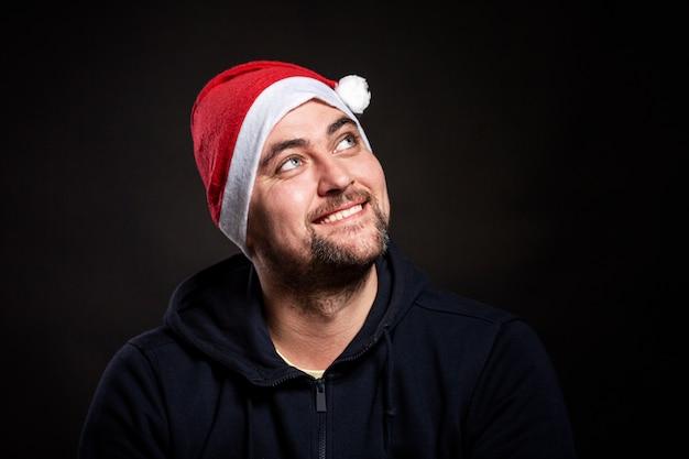 サンタクロースの帽子に笑みを浮かべてハンサムな若い男を見上げる