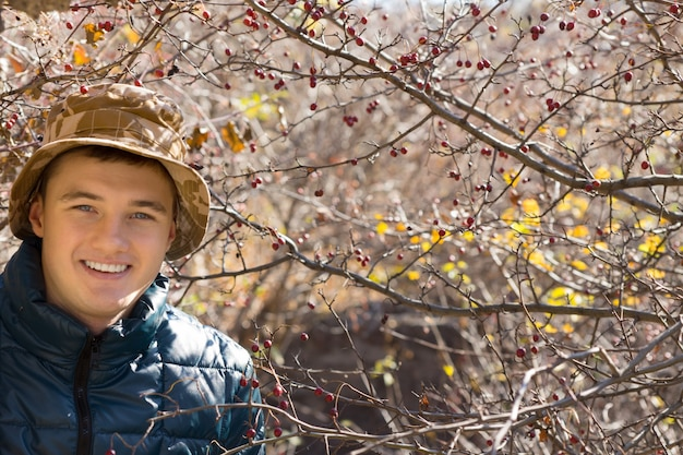 Smiling handsome young man wearing a hat and warm overcoat posing outdoors in autumn woodland looking at the camera with a friendly smile