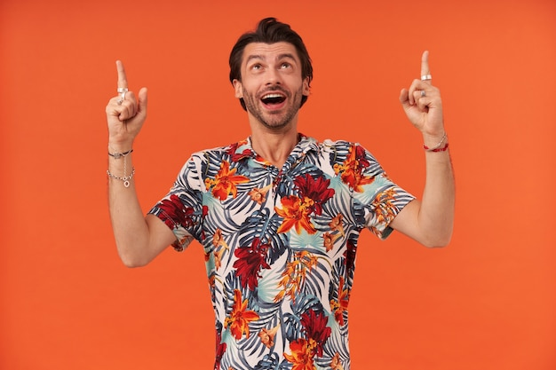 화려한 셔츠에 수염을 찾고 두 손에 손가락으로 빈 공간을 가리키는 웃는 잘 생긴 젊은 남자
