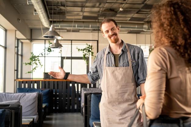 Улыбающийся красивый молодой официант в фартуке, показывая на свободный столик, приветствуя девушку в уютном кафе