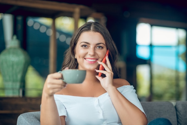 Smiling handsome young woman in off shoulder blouse drinking coffee and chatting on smartphone in cafe