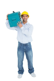 Smiling handyman in hard hat carrying a toolbox