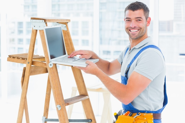 Smiling handyman using laptop by ladder in office