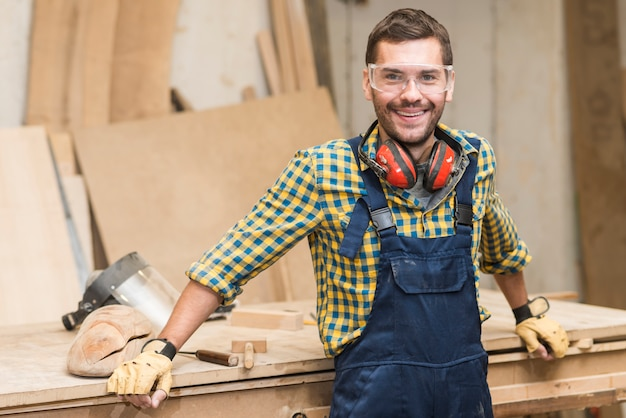 Smiling handyman wearing safety glasses looking at camera