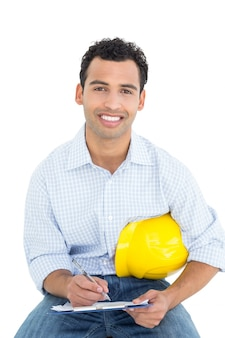 Smiling handyman with yellow hard hat writing in clipboard