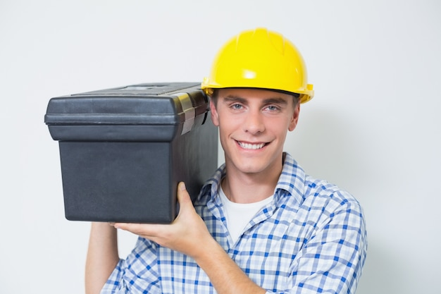 Smiling handyman in yellow hard hat carrying toolbox