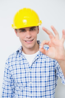 Smiling handyman in yellow hard hat gesturing okay sign