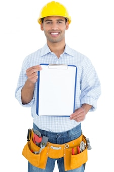 Smiling handyman in yellow hard hat holding a clipboard