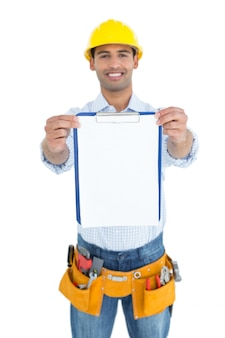 Smiling handyman in yellow hard hat holding clipboard