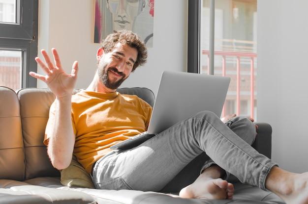 Счастливо улыбается и весело машет рукой, приветствуя и приветствуя вас или прощаясь