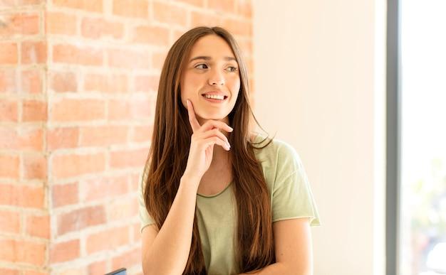 Счастливо улыбается и мечтает или сомневается, смотрит в сторону