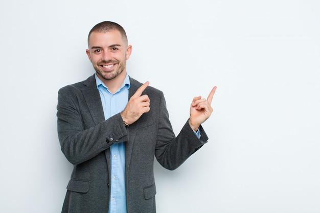 幸せそうに笑って、コピースペースでオブジェクトを示す両手で上向きと横向き