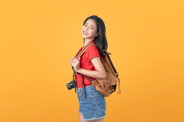Smiling happily asian woman traveler holding camera and backpack