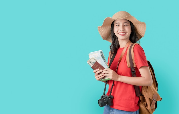 チケットと地図、青のお金でパスポートを保持しているアジア女性旅行者を幸せそうに笑っています。