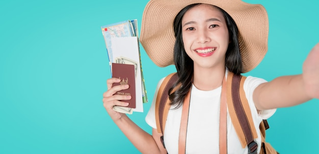 Smiling happily asian woman traveler holding passport with ticket and map, money.