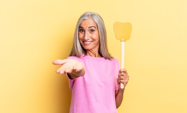 Smiling happily with friendly, confident, positive look, offering and showing an object or concept and holding a fly swatter
