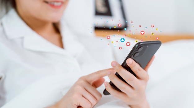 Smiling happily woman hand using smartphone and show heart icon social media. concept social network.