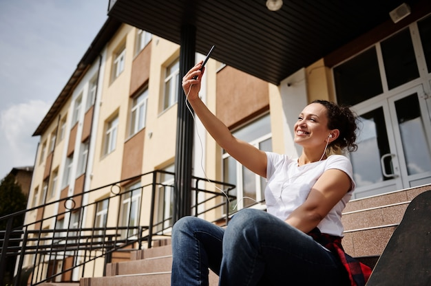 Smiling happy african american woman with headphones in casual clothing making selfie while sitting on steps on the background of yellow building