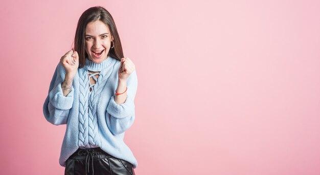 コピースペースとピンクの背景にスタジオで笑顔、幸せで勝利のブルネットの女の子