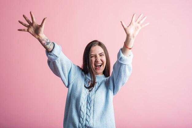 ピンクの背景にスタジオで笑顔、幸せで勝利のブルネットの女の子