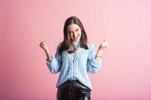 ピンクの背景の上のスタジオで笑顔、幸せで勝利のブルネットの女の子