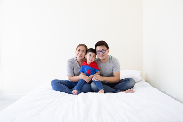 Smiling happy asian family and son wearing superhero suit sitting on white bed in the bedroom