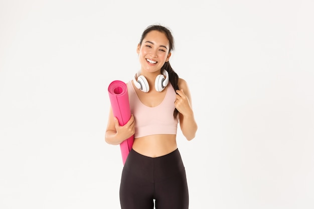 Smiling happy asian fitness girl in headphones and sportswear, carry rubber mat for workout or yoga, laughing carefree over