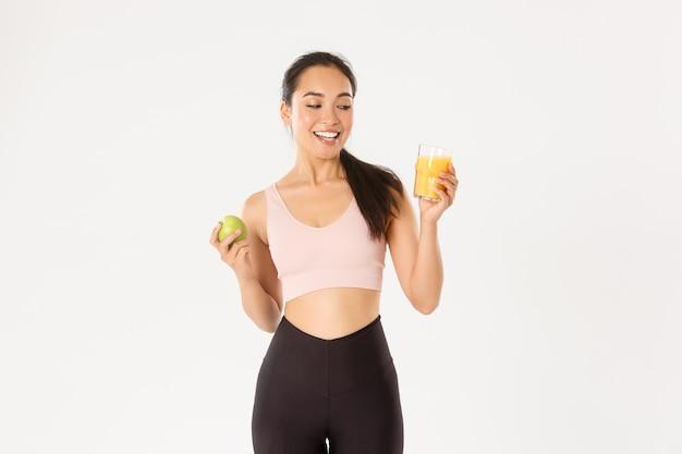 Улыбающаяся счастливая азиатская фитнес-девушка в спортивной одежде, смотрящая на апельсиновый сок, довольна, ест яблоко после продуктивной тренировки в тренажерном зале, на белом фоне.
