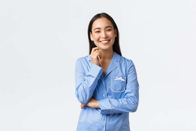 Улыбается счастливая азиатская девушка, стоя в пижаме и глядя на камеру оптимистично. студентка устраивает веселую ночевку с подругами, развлекается. девушка развлекается на пижамной вечеринке
