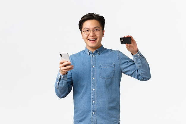 Улыбающийся счастливый азиатский парень в очках и повседневной одежде, использующий мобильный телефон для перевода денег на банковский счет, показывая кредитную карту с довольным выражением лица, довольный стоя на белом фоне.