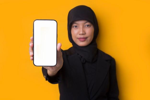 スマートフォンを示す笑顔幸せなアジアのイスラム教徒の実業家