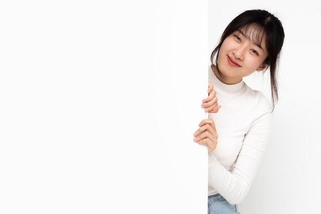 잡고 큰 흰색 포스터 뒤에 서서 웃는 행복 한 아시아 여자