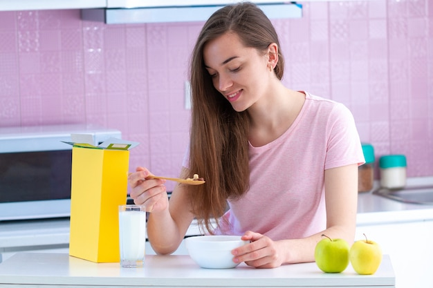 Smiling, happy attractive woman eating crispy chocolate balls for healthy cereals breakfast in morning in kitchen at home