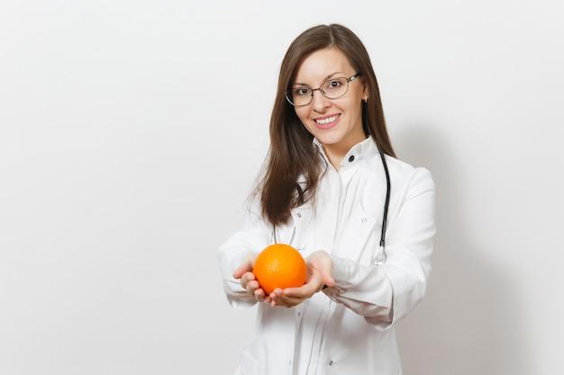 청진 기, 흰색 배경에 고립 된 안경 행복 매력적인 젊은 아가씨 의사 여자 웃 고. 오렌지를 들고 의료 가운에 여성 의사입니다. 의료 인력, 건강, 의학 개념입니다.