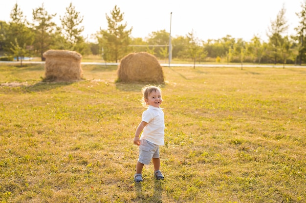 Smiling happy baby boy on natural background in summer