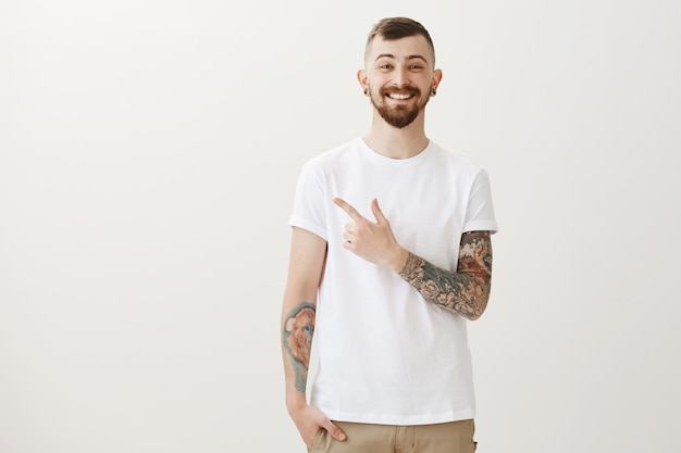 Smiling happy bearded man with tattoos and piercing pointing finger left