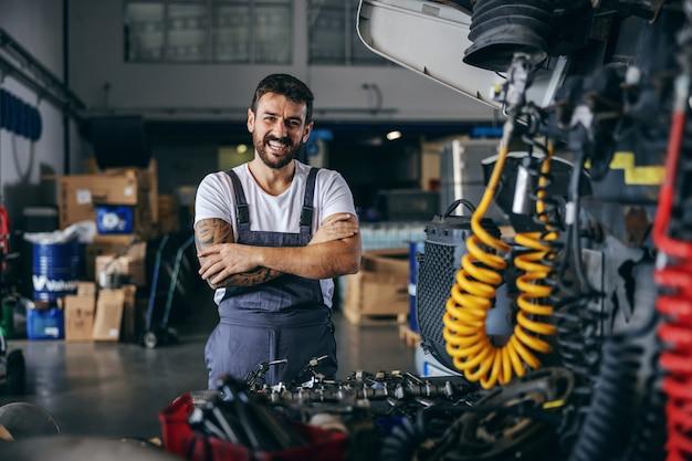 Улыбающийся счастливый бородатый татуированный рабочий в комбинезоне стоит рядом с грузовиком со скрещенными руками.