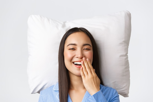 Smiling happy beautiful asian girl lying in bed on pillow in blue pajamas, waking up open eyes and yawning, morning routine of young woman. cute female in jammies staying bed, white background