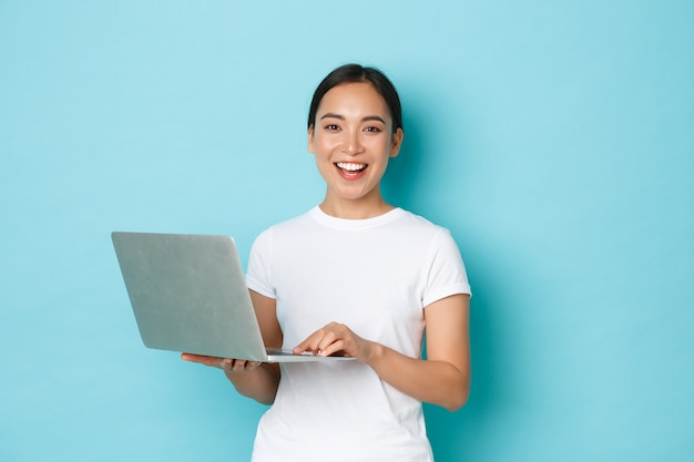Smiling happy, beautiful asian woman using laptop while standing over light blue wall, express cheerful attitude, working on project or shopping online