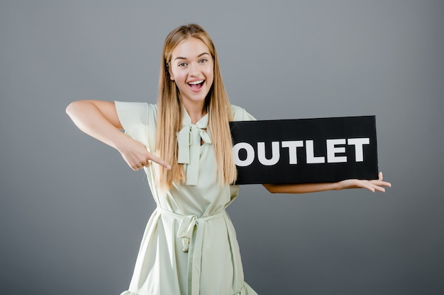 Smiling happy beautiful woman pointing finger at outlet sign isolated over grey