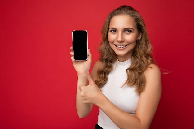 Улыбается счастливая красивая молодая блондинка в белой футболке, изолированной на красной поверхности