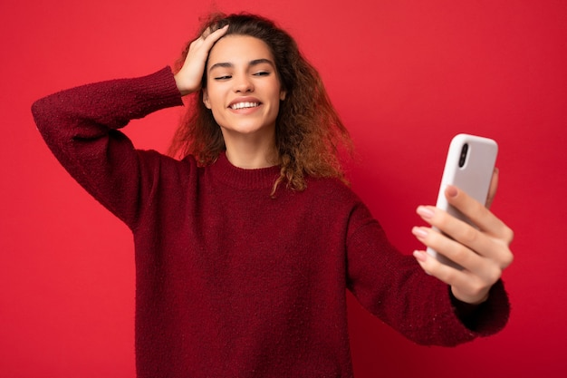빨간색으로 격리된 짙은 빨간색 스웨터를 입고 곱슬머리를 한 웃고 있는 행복한 아름다운 젊은 여성