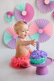 Smiling baby girl celebrating her first birthday, eating