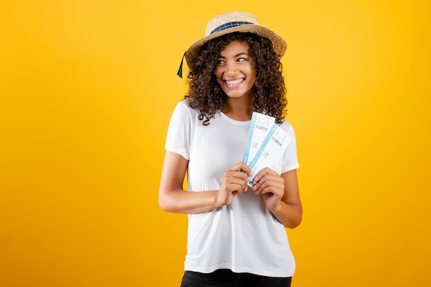 Smiling happy black woman with plane tickets wearing hat isolated over yellow