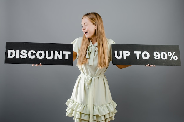 Smiling happy blonde girl with discount up to 90% sign isolated over grey