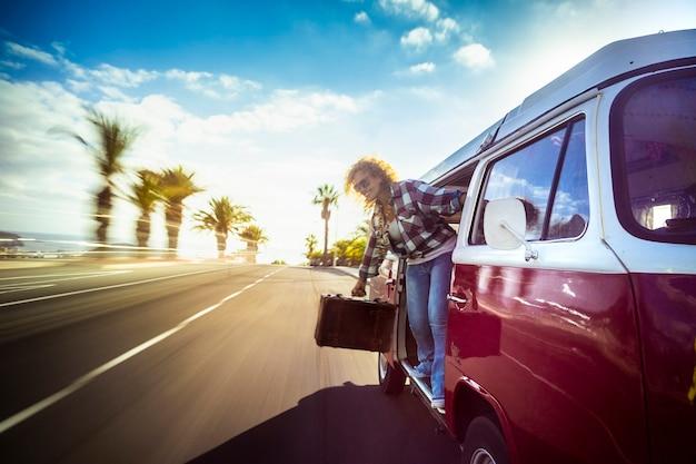 笑顔の幸せな金髪の女性は、飛行機やスカイダイビングの活動のように、開いたドアから通りを見ながら、道路の赤い古いバンに高速で移動します