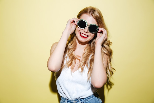 Smiling happy blonde woman wearing sunglasses and posing